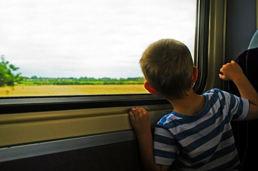 Un enfant regardant par la fenêtre durant son voyage en train